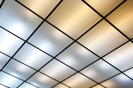 Fluorescent lamps on the modern ceiling. Luminous ceiling of square tiles. Standard-Bild