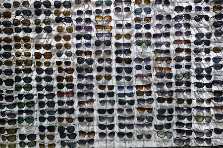 Many sunglasses on white wall background. Showcase with glasses.
