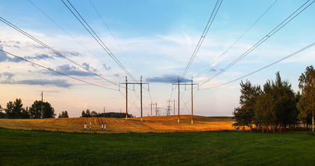 over voltage: Pillars with high voltage electric wires over the field after harvest in the countryside.