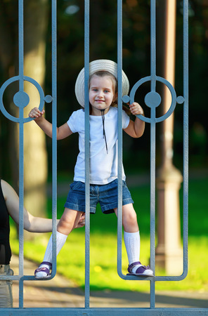 vertical bars: Happy child climbs on the bars of a metal fence. Warm sunny summer day. Vertical shot. Stock Photo