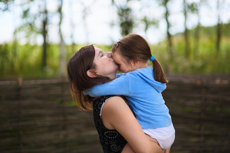 keeps: A mothers love. Mom keeps little daughter in her arms and kisses her on the forehead. Selective on the faces of the models.