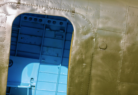 Fragment of old military green aircraft with open doorways close-up.
