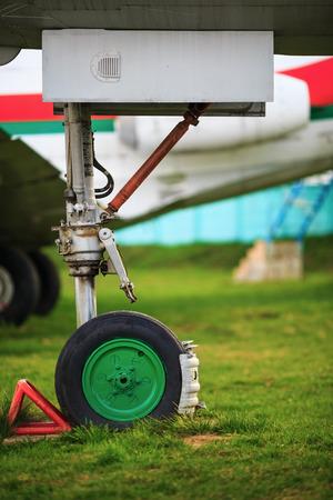 aluminum airplane: Front landing gear light aircraft on green grass. Shallow depth of field. Selective focus. Stock Photo