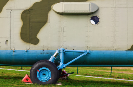 damper: A fragment of the old heavy truck military helicopter close-up. Landing gear of an helicopter on the green grass.