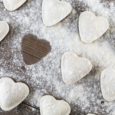 semimanufactures: Cooking ravioli.  Raw dumplings in the shape of hearts, sprinkle with flour, on dark wooden table. Top view.