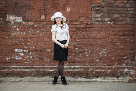 Photo of a woman in a white hat, blouse and black skirt, standing against the backdrop of an old vintage brown brick wall. Space for text. photo