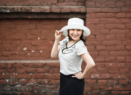 A smiling young woman in a white blouse and a hat posing against the backdrop of an old vintage brown brick wall. Female hand holds a hat.  Photo in retro style. Selective focus on model. photo
