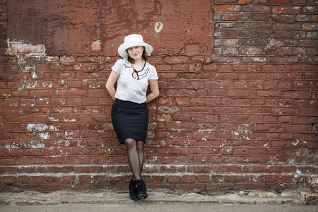 Pretty young brunette woman in a white hat blouse and black skirt posing outdoor in old vintage brown brick wall background. Girl is leaning against the wall. Space for text. photo