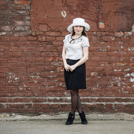 Photo of a woman in a white hat blouse and black skirt standing against the backdrop of an old vintage brown brick wall. Space for text. photo