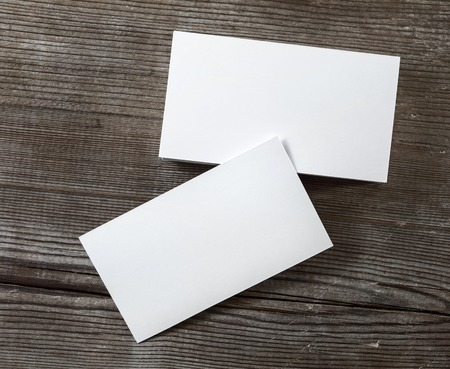 Photo of blank business cards on a dark wooden background. Mockup for branding identity. Top view. Standard-Bild