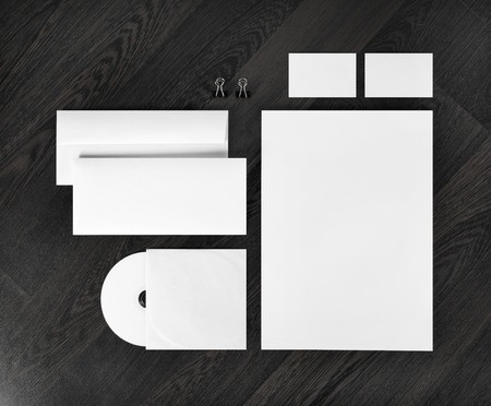 ides: Blank stationery and corporate identity template on dark wooden background. For design presentations and portfolios. Top view.