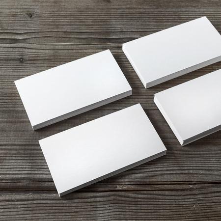 Reeks lege witte adreskaartjes op een donkere houten achtergrond. Sjabloon voor branding van identiteit. Ondiepe scherptediepte.