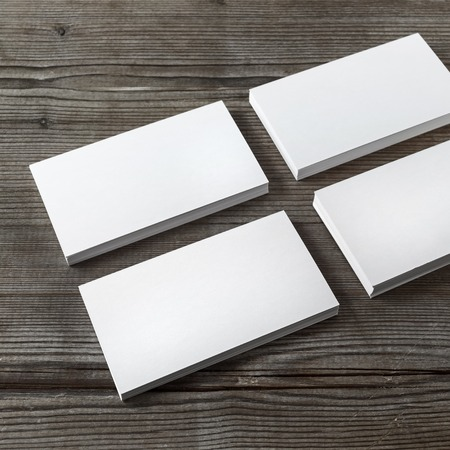 Set of blank white business cards on a dark wooden background. Template for branding identity. Shallow depth of field. Stok Fotoğraf