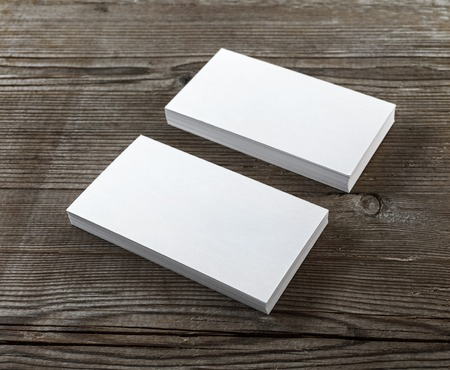 ides: Two stacks of blank business cards on a dark wooden background. Template for branding identity. Shallow depth of field. Selective focus.
