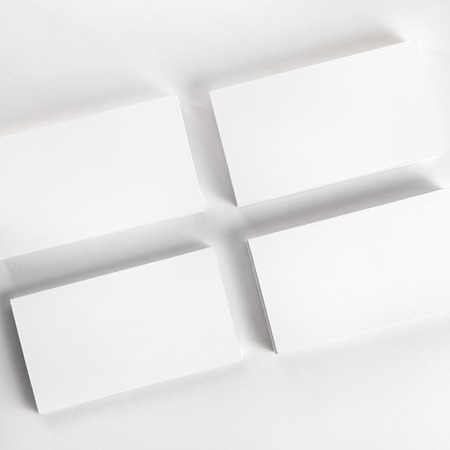 Photo of blank business cards on a light gray background. Template for branding identity. Top view.