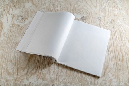 Blank opened magazine on light wooden background with soft shadows. For design presentations and portfolios.