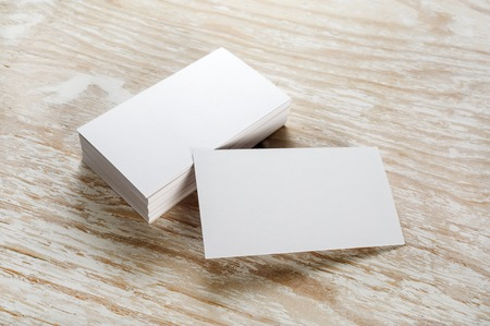 Photo of blank business cards with soft shadows on light wooden background. For design presentations and portfolios. Archivio Fotografico