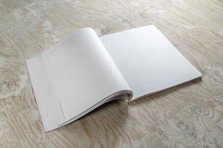 the brochure: Blank magazine folleto abierto sobre fondo de madera con sombras suaves. Mock-up para dise�adores gr�ficos carteras.