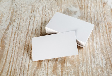 Blank business cards with soft shadows on light wooden background. Template for ID.