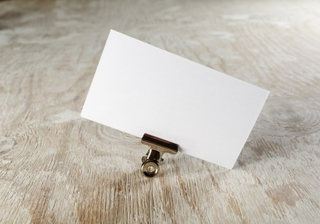 Photo of blank business card with soft shadow on light wooden background. Mock-up for branding identity.