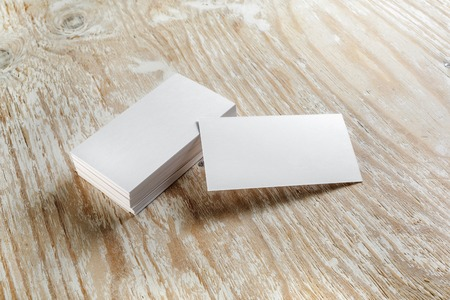 Blank business cards with soft shadows on light wooden background. Template for design presentations and portfolios. Studio shot. Foto de archivo