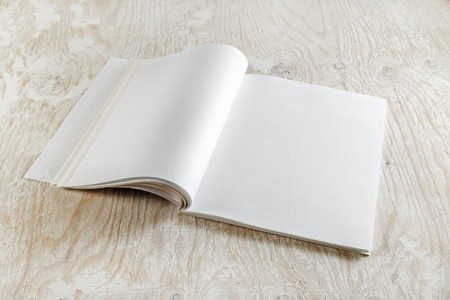 Blank opened brochure magazine on wooden background with soft shadows.  Template for graphic designers portfolios.