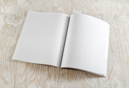 Blank opened book on light wooden background with soft shadows. Template for graphic designers portfolios. Top view.