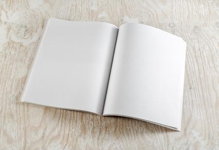 Blank otworzył książkę na jasnym tle drewnianych z miękkich cieni. Szablon dla grafików portfelach. Widok z góry.