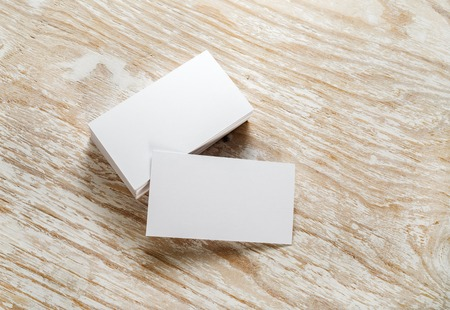Blanco visitekaartjes met zachte schaduwen op lichte houten achtergrond. Sjabloon voor het ontwerp presentaties en portefeuilles. Studio-opname. Stockfoto