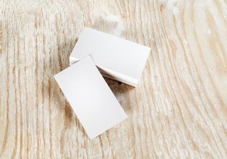 branding: Blank business cards on light wooden background. Template for branding identity. Top view.