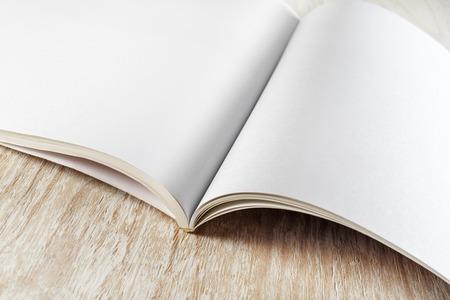 Fragment pustej otwartej broszury na jasnym tle drewnianych z miękkich cieni zbliżeniu. Do prezentacji projektowych i portfeli.