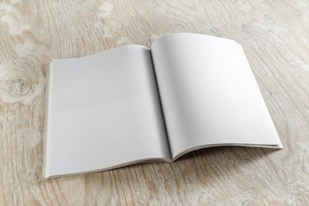 marca libros: Revista abierto en blanco sobre fondo de madera clara con sombras suaves. Para las presentaciones de diseño y carteras.