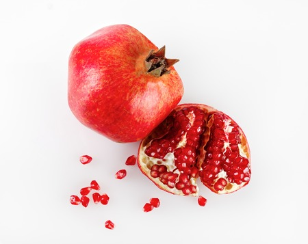 Ripe pomegranate and its half with reflection on a light background. Studio shot. Top view.