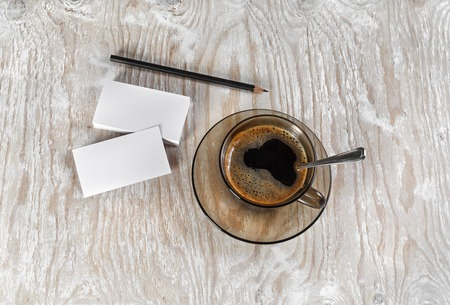 A cup of coffee, business cards and a pencil on a background of a wooden table. Top view.