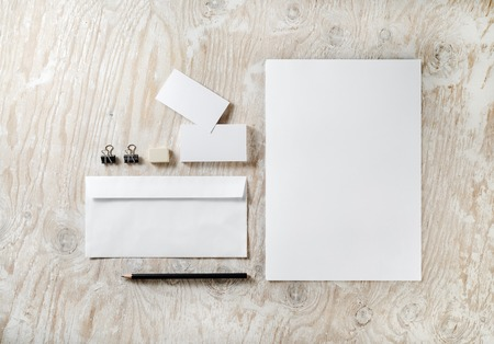 Photo of blank stationery set on light wooden background. Template for design presentations and portfolios.
