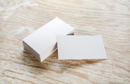 Photo of blank business cards on a wooden background. Template for ID.