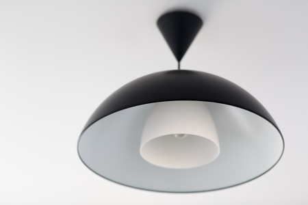 lighting fixtures: Big black chandelier. Lighting fixtures. Shallow depth of field. Selective focus. Stock Photo