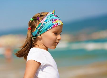 profil: Dziewczynka dla dzieci z chustą na głowie na rozmytym tle niebieskiego nieba i morza. Gorąco słoneczny letni dzień. Selektywne fokus.