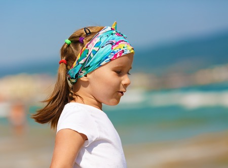 one little girl: Profile of baby girl with a bandanna on his head on a blurred background of blue sky and sea. Hot sunny summer day. Selective focus.