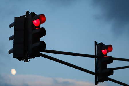light color: Traffic light with red light against the evening sky. Shallow depth of field. Selective focus.