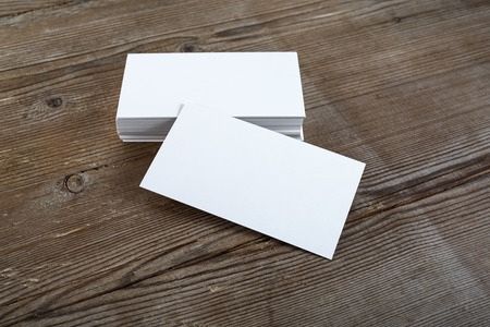 Photo of blank business cards with soft shadows on dark wooden background. For design presentations and portfolios. Standard-Bild