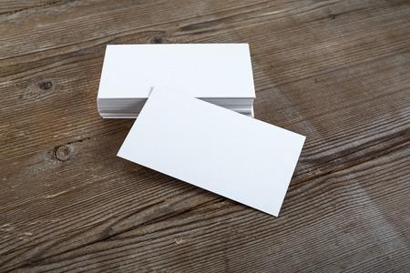 Zdjęcie puste wizytówki z miękkich cieni na ciemnym tle drewnianym. Do prezentacji i portfeli projektowych.