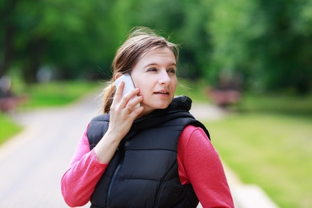 communicates: Pretty young woman communicates via a mobile phone in the park. Selective focus on the model.
