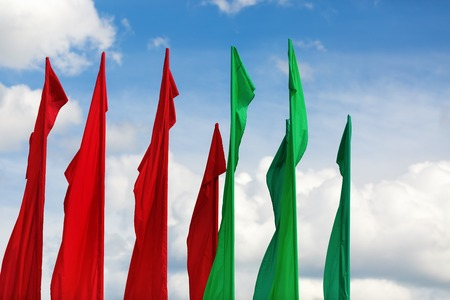 flagpoles: Several flagpoles with vertical green and red flag against a blue sky. Stock Photo
