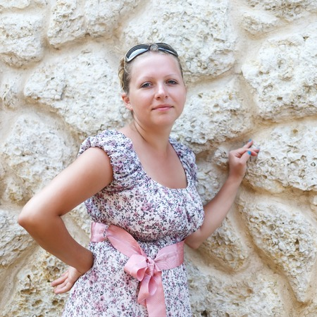 sundress: Pretty young woman in a sundress leaning his arm on the limestone wall. Stock Photo