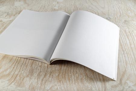 Foto. Open brochure tijdschrift met zachte schaduwen op houten achtergrond. Vintage stijl foto. Mock-up voor grafisch ontwerpers portefeuilles.