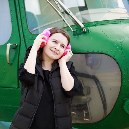 pink fur: Woman listening to music with pink fur headphones over green helicopter cabin