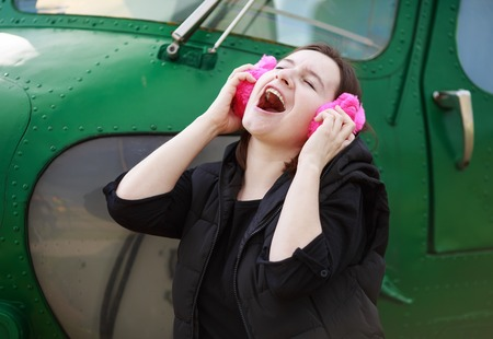 pink fur: Woman enjoying music with pink fur headphones on the background of the green helicopter cabin. She enjoys music.