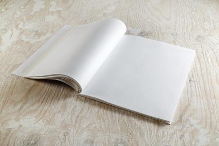 空白開設パンフレット ソフト シャドウと木製の背景に雑誌の写真。グラフィック デザイナーのポートフォリオのためのモックアップ。