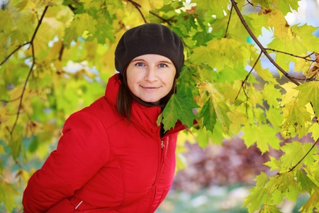 green beret: Girl in a beret and red jacket on the background of green and yellow autumn maple leaves. Woman looking into the camera. Selective focus on model.